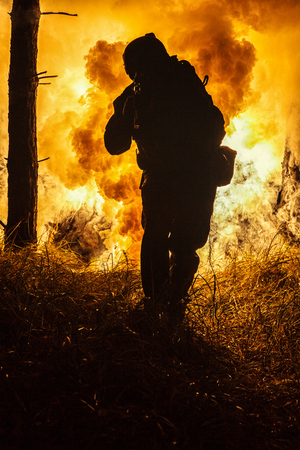 blowup: Backlit silhouette of special forces marine operator in forest on fire explosion background. Battle, bombs exploding, fighting no matter what