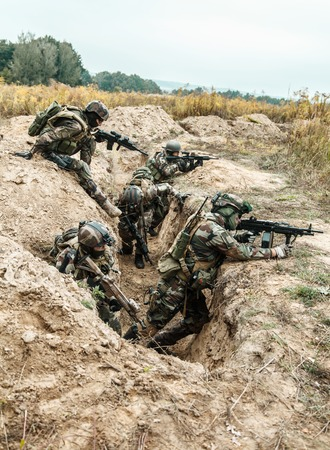 occupying: Squad of elite french paratroopers of 1st Marine Infantry Parachute Regiment RPIMA taking control enemy trenches, securing positions