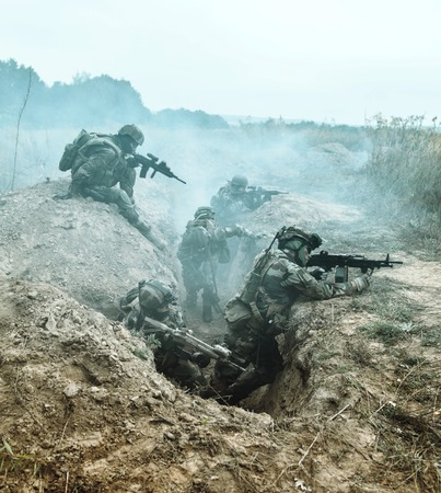 Squad of elite french paratroopers of 1st Marine Infantry Parachute Regiment RPIMA in action in enemy trenches filled with gunpowder smoke Stock Photo - 74338780