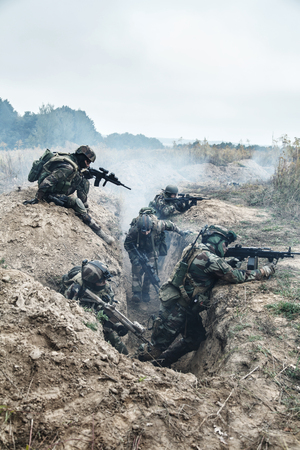seizing: Squad of elite french paratroopers of 1st Marine Infantry Parachute Regiment RPIMA in action in enemy trenches filled with gunpowder smoke