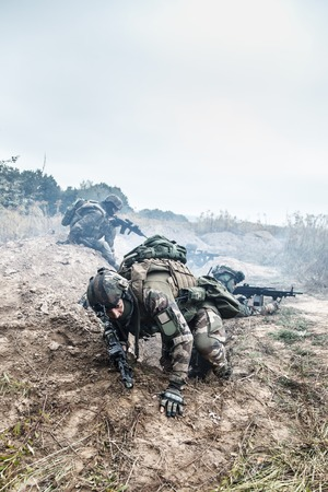 seizing: Squad of elite french paratroopers of 1st Marine Infantry Parachute Regiment RPIMA in action in enemy trenches one militant jumping out