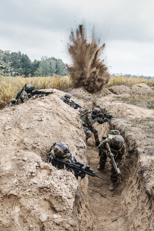 Squad of elite french paratroopers of 1st Marine Infantry Parachute Regiment RPIMA in action in enemy trenches, militants and machine gunner