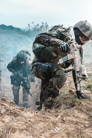 Two french paratroopers of 1st Marine Infantry Parachute Regiment RPIMA, in action jumping out of enemy trench filled with gunpowder smoke Stock Photo