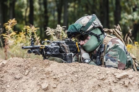 Machine gunner of 1st Marine Infantry Parachute Regiment RPIMA firing from defensive position trench