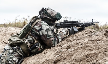 gunner: Machine gunner of 1st Marine Infantry Parachute Regiment RPIMA firing from defensive position trench, profile side view