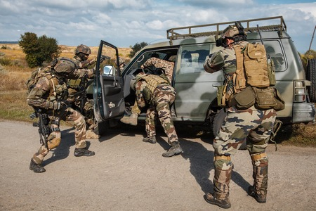 occupying: Squad of elite french paratroopers of 1st Marine Infantry Parachute Regiment RPIMA detaining terrorist in the car Stock Photo