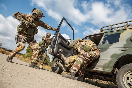 occupying: Squad of elite french paratroopers of 1st Marine Infantry Parachute Regiment RPIMA detaining terrorist in the car, low angle view