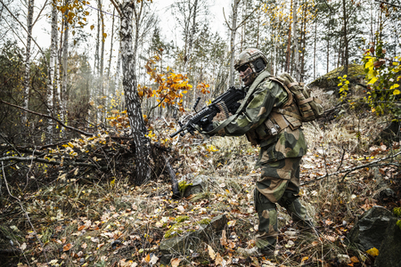 gunner: Norwegian Rapid reaction special forces FSK soldier patrolling in the forest. Field camo uniforms, knee pads, combat helmet and eye-wear goggles are on