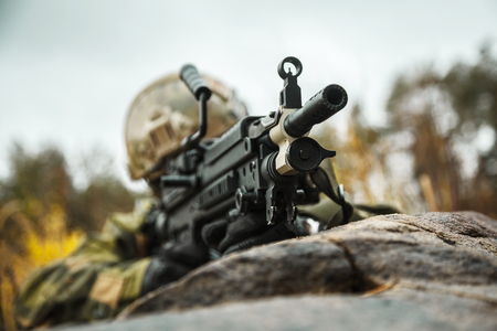 patrolling: Norwegian Rapid reaction special forces FSK soldier firing in the forest. Field camo uniforms, combat helmet and eye-wear goggles are on