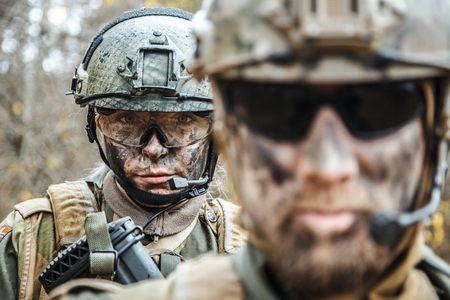 Norwegian Armed Forces Special Command FSK male and female soldiers closeup portrait. Radio and headset are on. Foreground defocus