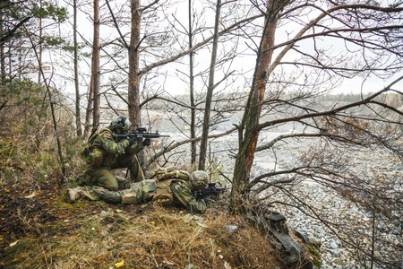 Norwegian Rapid reaction special forces FSK soldiers in field uniforms scouting in the forest trees