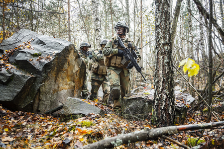 patrolling: Norwegian Rapid reaction special forces FSK male and female soldiers in field uniforms patrolling in the forest trees