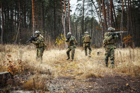 patrolling: Norwegian Rapid reaction special forces FSK soldiers in field uniforms patrolling in the forest trees