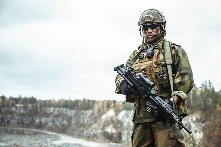 patrolling: Norwegian Rapid reaction special forces FSK soldier patrolling in the forest. Field camo uniforms, combat helmet and eye-wear goggles are on