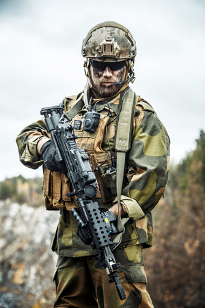 Norwegian Rapid reaction special forces FSK soldier patrolling in the forest. Painted face, combat helmet and eye-wear goggles are on