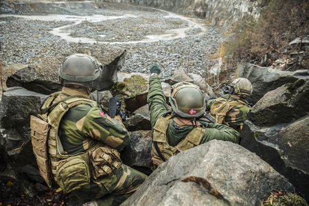 Patrol of norwegian Rapid reaction special forces FSK soldiers in field uniforms in ambush among the rocks guarding perimeter waiting enemy Stock Photo
