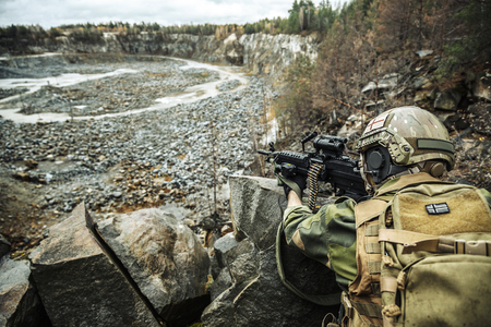 Norwegian Rapid reaction special forces FSK soldier in field uniforms in ambush among the rocks guarding perimeter waiting enemy Stock Photo