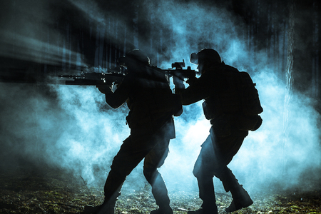 billow: Black silhouettes of pair of soldiers in the smoke moving in battle operation. Back light