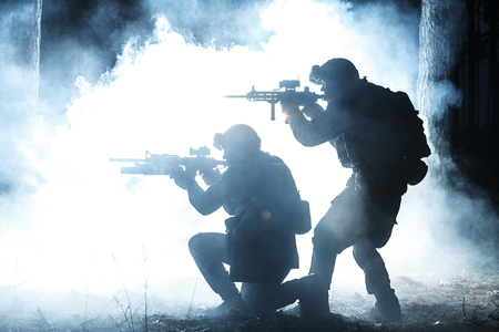 operation light: Black silhouettes of pair of soldiers in the smoke moving in battle operation. Back light