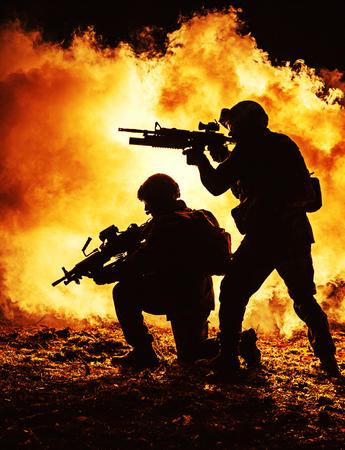 煙の中の兵士のペアの黒いシルエット火災の燃焼戦い操作で移動します。バックライト