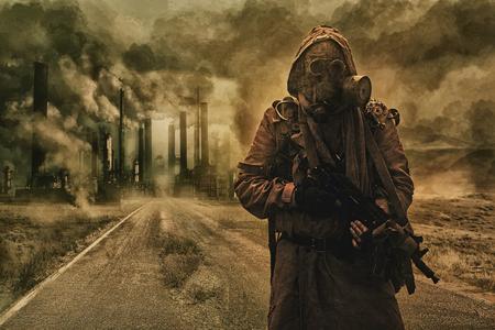 Post-apokalyptische Luftverschmutzung. Überlebender in Fetzen und Gasmaske auf dem Hintergrund der Rohre auf verlassener Straße. Naturschutzkonzept