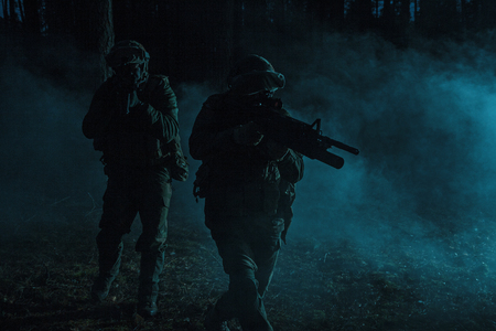 Pair of soldiers in the smoke in action on battle operation. Dark gloomy night, they moving stealthy