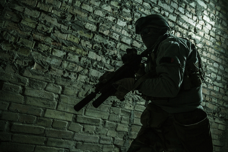 Special forces operator pointing weapon in the dark. Combat helmet, and bulletproof vest are on. Low key image, shadow soldier