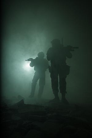 煙霧戦い操作で移動中の兵士の組の黒いシルエットは。バックライト 写真素材