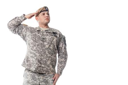 batallón: National Anthem is played. Army Ranger from Special Troops Battalion in universal Camouflage pattern Uniforms and Tan beret with Ranger Regiment crest is standing to attention and saluting proudly with honor and respect. Service to his country concept. Na