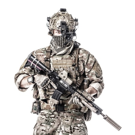 Army Ranger in field Uniforms with weapon, plate carrier and combat helmet are on, his face closed by Shemagh Kufiya scarf. Studio shot Stock Photo