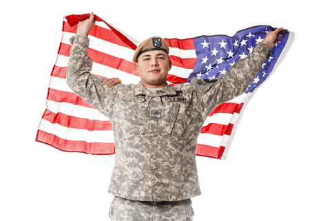 Army Ranger from Special Troops Battalion in universal Camouflage pattern Uniforms and Tan beret with Ranger Regiment crest standing and holding waving US flag in his hands proudly. National holidays: Veterans Day, Memorial Day Stock Photo