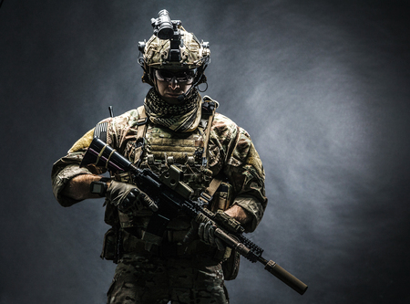 Army soldier in Combat Uniforms with assault rifle, plate carrier and combat helmet are on, Shemagh Kufiya scarf on his neck. Studio shot, dark background Stock Photo