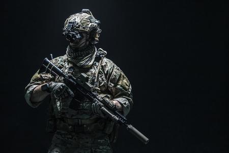アサルトライフル、プレート キャリアや戦闘のヘルメットと戦闘服の陸軍兵士に、彼の首にシェマグ Kufiya スカーフ。スタジオ撮影、暗い背景