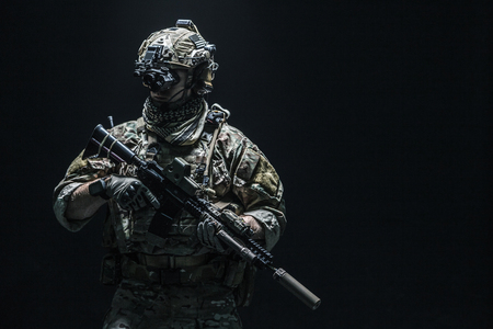Army soldier in Combat Uniforms with assault rifle, plate carrier and combat helmet are on, Shemagh Kufiya scarf on his neck. Studio shot, dark background 版權商用圖片