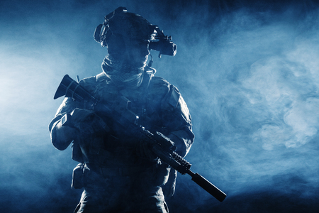 Army soldier in Combat Uniforms with assault rifle, plate carrier and combat helmet are on, Shemagh Kufiya scarf on his neck. Studio contour silhouette shot, backlight, dark glowing smoke background Stock Photo