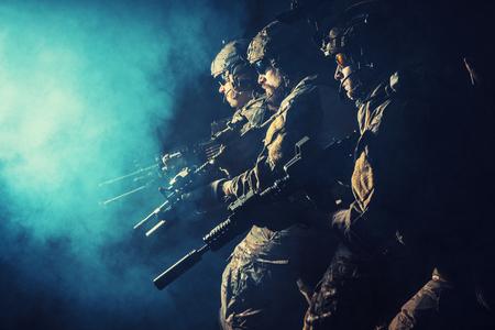 危険に直面して並んでライフルで戦う制服で治安部隊のグループ。敵に直面して、それらは大胆に立ち、国を守るために準備ができています。スタ 写真素材