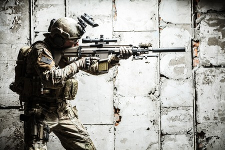 Army Ranger moving along the concrete wall on mission Stock Photo