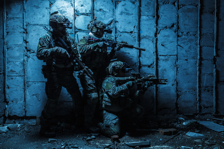 Squad of Army Rangers with rifle and machine gun moving along the concrete wall of ruined destroyed building on mission. They are ready to start firing if enemy appear. Outdoor location shot, darkness of night, dim light