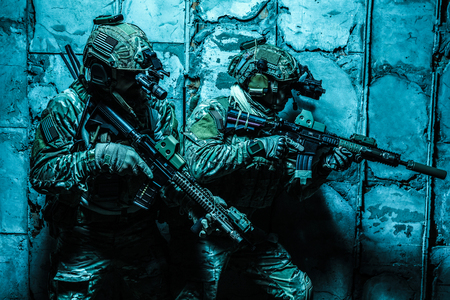 Squad of Army Rangers moving along the concrete wall on mission. They are ready to contact with enemy and to kill. Outdoor location shot, darkness of night, dim light Banco de Imagens