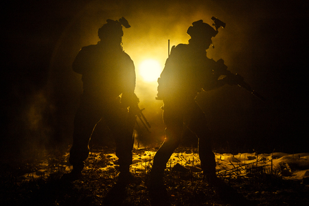 blowup: Dark silhouettes of pair of soldiers moving in battle operation. Back light