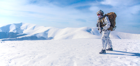 Army serviceman in winter camo somewhere in the Arctic. He wears chest rig, backpack, suffers from extreme cold, strong wind, but endures while mission continues, running moving across snow desert