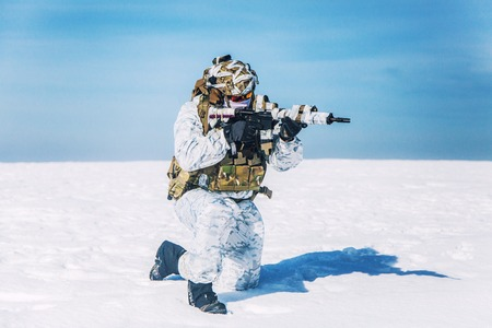 Army soldier with weapon in the Arctic. He wears chest rig, backpack, suffers from extreme cold, strong wind, but endures while mission continues, killing in snow desert. Shooting in kneeling position Stock Photo