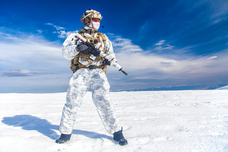 Army serviceman in winter camo somewhere in the Arctic. He wears chest rig and huge backpack, suffers from the extreme cold and strong wind, but endures while mission continues. Blue sky background