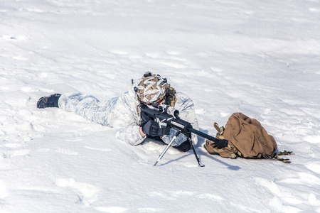 Army soldier with Sniper rifle in action in the Arctic. He lies in the snow desert, suffering from extreme cold, but waiting as long as enemies appear to kill them 版權商用圖片