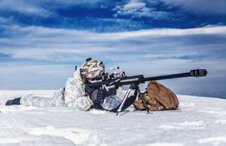 Army soldier with Sniper rifle in action in the Arctic. He lies in the snow desert, suffering from extreme cold, but waiting as long as enemies appear to kill them Stock Photo