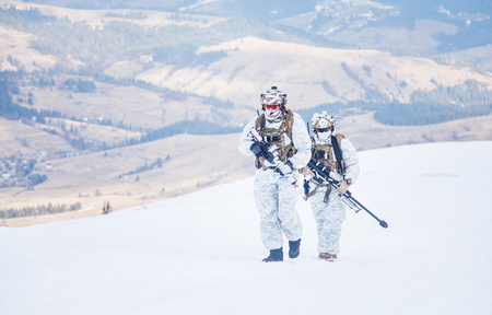 Army servicemen in winter camo somewhere in the mountains. Walking moving across snow desert despite bad weather wind and cold, holding weapons - assault and sniper rifle. Full body portrait