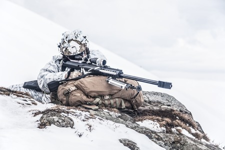Army soldier with Sniper rifle in action in the Arctic. He lies among the cold rocks and stones, almost freezing to death, but waiting as long as enemies appear to kill them. Duty, service and loyalty