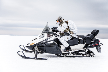 Army soldier in winter camo somewhere in the Arctic moving across the snow field riding tracked snowmobile Stock Photo