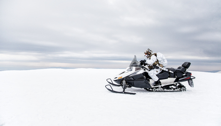 Army soldier in winter camo somewhere in the Arctic moving across the snow field riding tracked snowmobile Imagens
