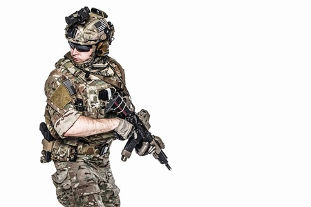 his shirt sleeves: Elite member of US Army rangers in combat uniforms with his shirt sleeves rolled up, in helmet, eyewear and night vision goggles, in turning around in action. Studio shot, white background